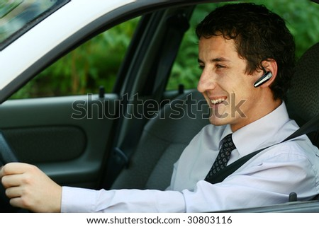 Smiling businessman driving a car with headset
