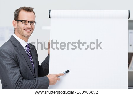 Smiling businessman giving a presentation pointing with his marker pen to a blank flipchart with copyspace for your text - stock photo
