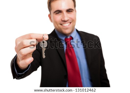 Smiling businessman giving keys to you. Isolated on white