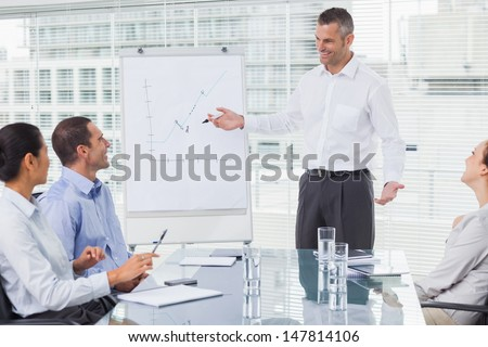 Smiling businessman giving presentation to his colleagues in bright office - stock photo