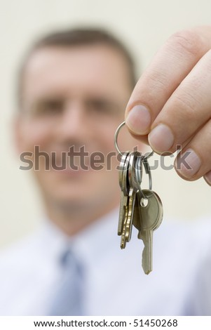 Smiling businessman handing over keys - stock photo