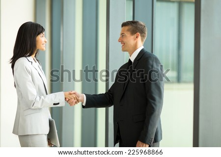 smiling businessman handshaking with businesswoman in office - stock photo
