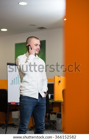 Smiling businessman having mobile phone conversation while standing with digital tablet in office building, happy intelligent man in suit talking on cell telephone and holding touch pad in the hand