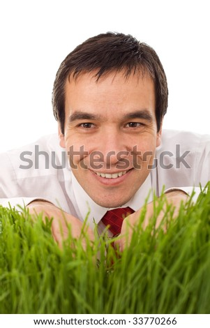 Smiling businessman hiding behind grass - isolated - stock photo