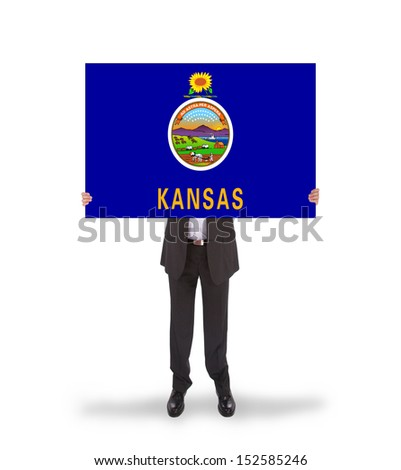 Smiling businessman holding a big card, flag of Kansas, isolated on white - stock photo