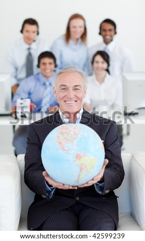 Smiling businessman holding a terrestrial globe with his team in the background - stock photo