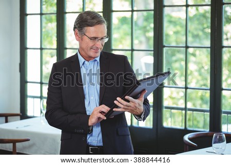 Smiling businessman holding a wallet in a restaurant
