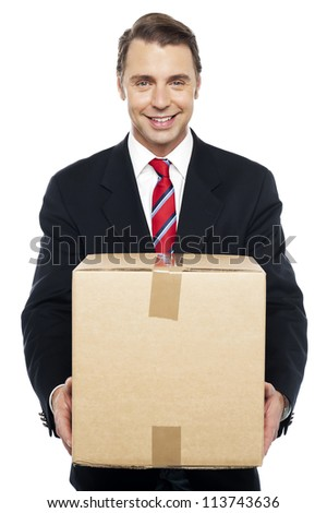 Smiling businessman holding cardboard box, being asked to change his cube - stock photo