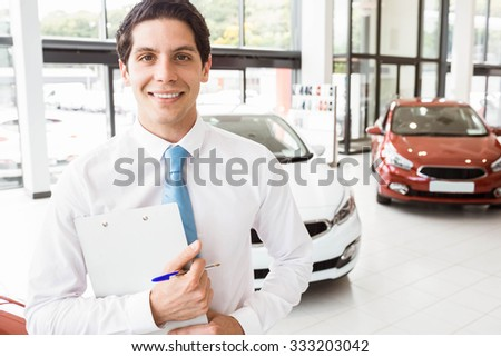 Smiling businessman holding clipboard at new car showroom - stock photo