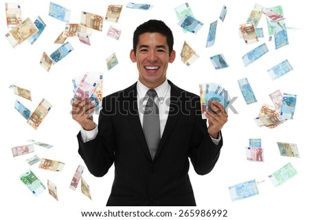 Smiling businessman holding Euro in a money rain storm. looking at camera. concept. - stock photo
