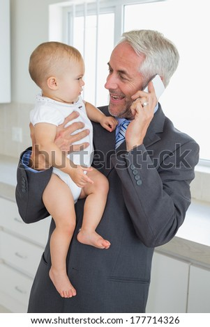 Smiling businessman holding his baby in the morning before work at home in the kitchen - stock photo