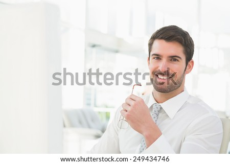 Smiling businessman holding his glasses in his office - stock photo
