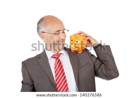 smiling businessman holding piggy bank on his shoulder - stock photo