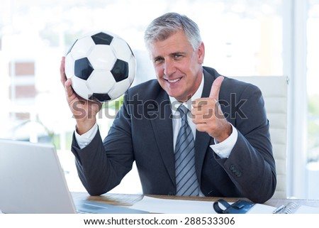 Smiling businessman holding soccer ball with thumbs up in his office - stock photo