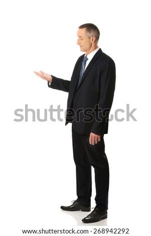Smiling businessman holding something on his palm. - stock photo