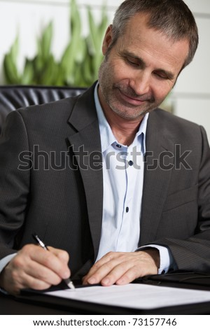 Smiling businessman in dark suit and blue shirt sitting at office desk and signing a contract, looking at signature.