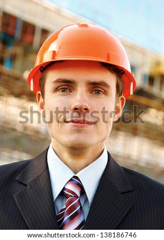 Smiling businessman in helmet while building - stock photo