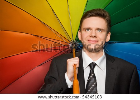 smiling businessman in suit with multi-coloured umbrella - stock photo