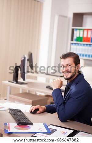 Smiling Businessman in suit working in his office. Business and corporate. Image of young succesful entrepreneur at his work place.