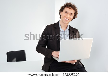 Smiling businessman leaning on the table with laptop computer and looking at camera