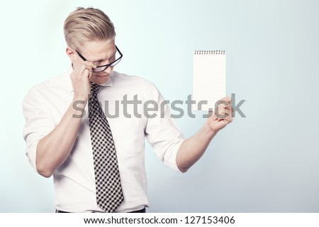 Smiling businessman looking at blank notepad with space for text while holding it, isolated. - stock photo
