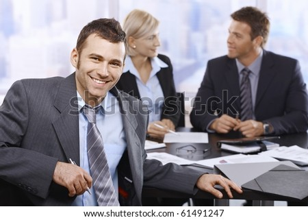 Smiling businessman looking at camera sitting at meeting table, coworkers in background.? - stock photo