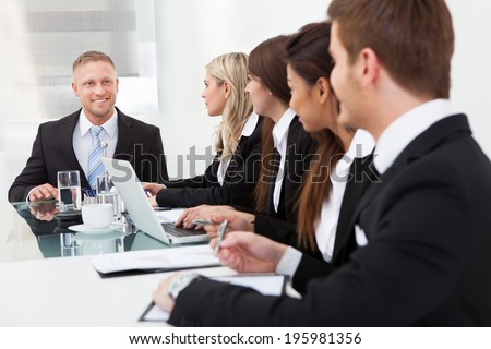 Smiling businessman looking at colleagues during meeting in office - stock photo