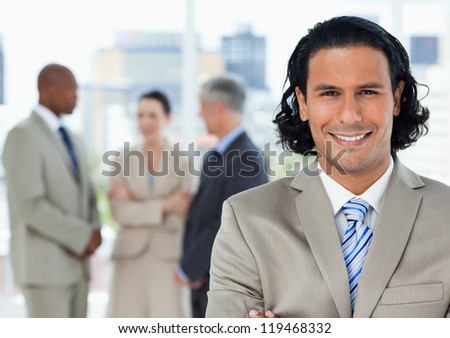 Smiling businessman looking at the camera in front of his team - stock photo