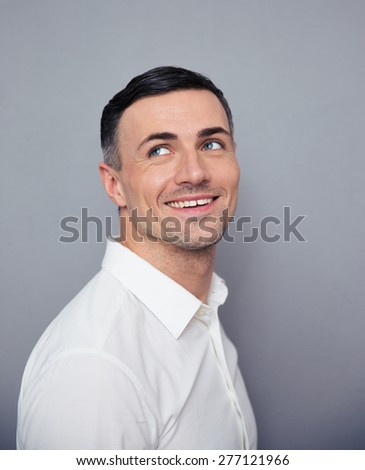 Smiling businessman looking away at copyspace over gray background - stock photo