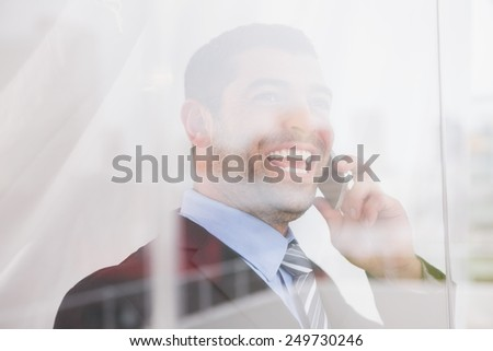Smiling businessman looking out window on the phone in his office