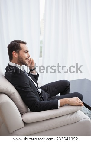 Smiling businessman making a call on his couch at home in the living room - stock photo