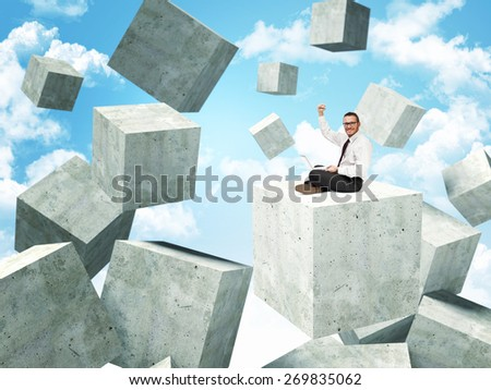 smiling businessman on 3d concrete abstract cubes - stock photo