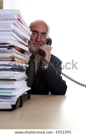 Smiling businessman on telephone with pile of paperwork