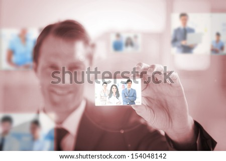 Smiling businessman picking a business team picture on red background - stock photo