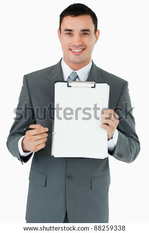 Smiling businessman pointing with pen at clipboard against a white background