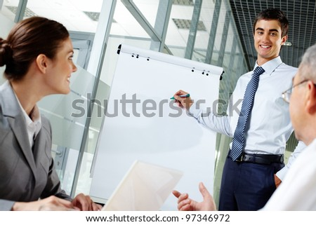 Smiling businessman presenting new project to his partners on a whiteboard - stock photo