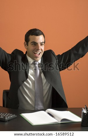 Smiling businessman seated at his computer throwing his arms up in jubilation. Vertically framed photo. - stock photo