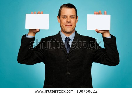 Smiling businessman showing two blank white placards to camera - stock photo
