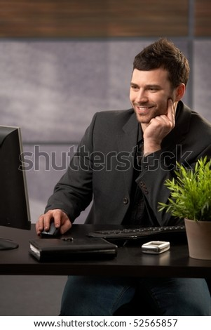 Smiling businessman sitting at desk using desktop computer, hand on mouse, looking at screen. - stock photo