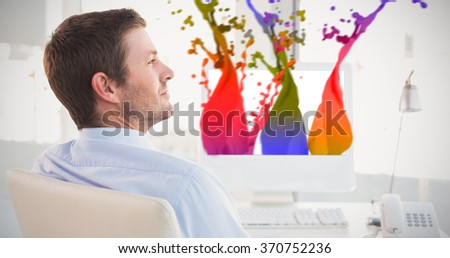 Smiling businessman sitting at his desk against pink paint splashes and drops - stock photo