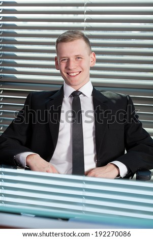 Smiling businessman sitting in his office, vertical
