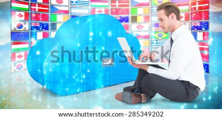 Smiling businessman sitting on floor using laptop against digitally generated black and blue matrix - stock photo