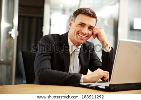 Smiling businessman sitting with laptop at office - stock photo