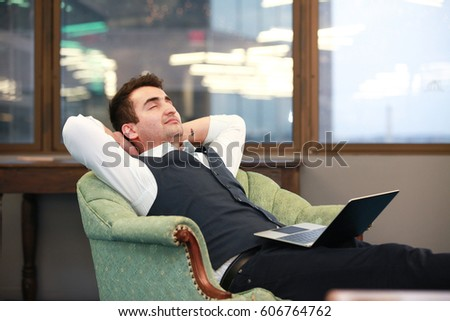 Smiling businessman sleeping in armchair with the laptop in Arlington city, Virginia.