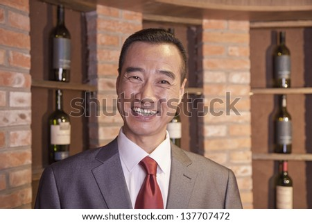 Smiling Businessman Standing by Wine Bottles - stock photo