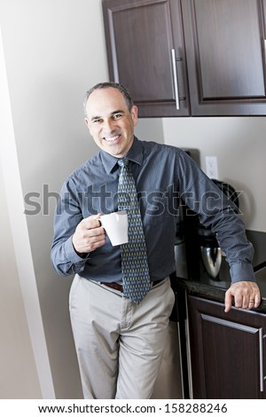 Smiling businessman standing holding coffee cup in office kitchen - stock photo