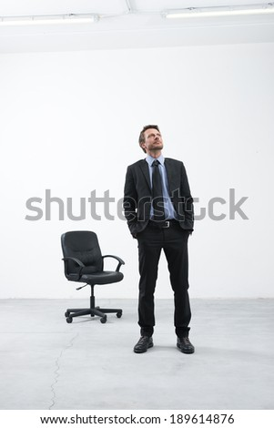 Smiling businessman standing in his new empty office with hands in pockets looking around.
