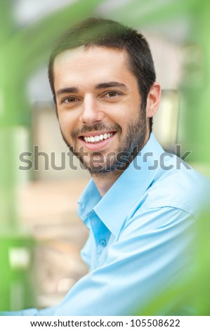 Smiling businessman standing in the green outdoors - stock photo