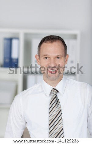 Smiling businessman standing with office files background - stock photo