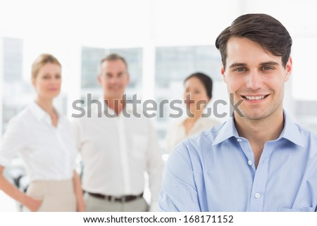 Smiling businessman standing with team behind him in the office